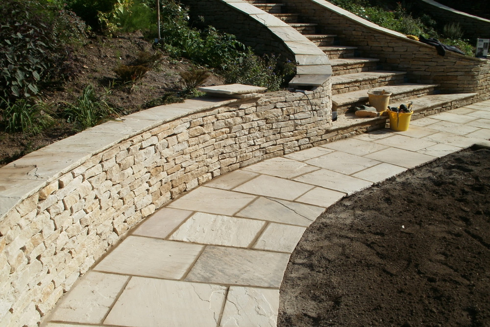 Curved slabbed pathway and Cotswold Stone wall
